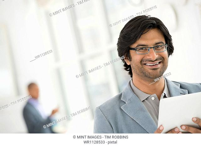 A business environment, a light airy city office. Business people. A man in glasses using a digital tablet