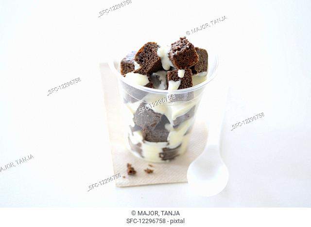 Brownies with vanilla sauce in a takeaway cup