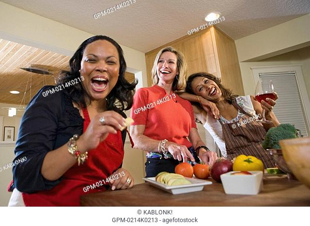 Happy multi-ethnic women holding fruit and red wine in modern kitchen