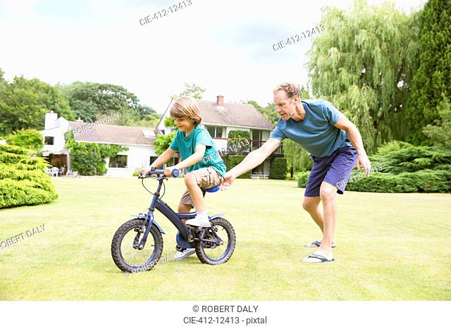 Father pushing son on bicycle in backyard