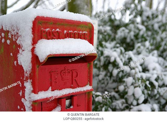 England, Essex, Saffron Walden, Snow covers a traditional British rural post box in Essex
