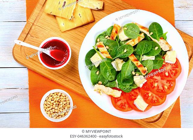healthy delicious low calories spinach, grilled chicken breast, tomato salad with creamy soft brie cheese and pine nuts on white plate on wooden cutting board...