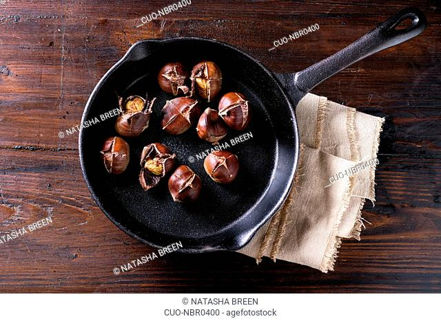 Heap of grilled edible chestnuts in cast iron skillet over dark wooden surface with textile napkin. Top view