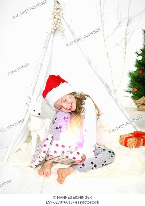 sibling with christmas hats at geschenkeauspacken