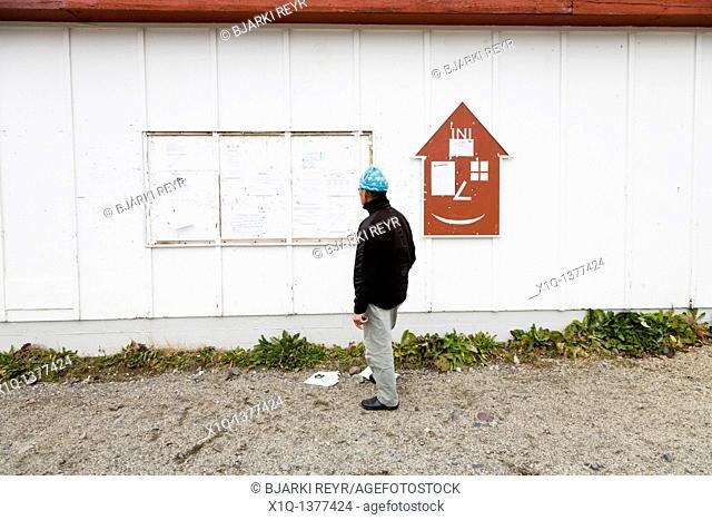 Man reading a community notice board, Narsaq, South Greenland