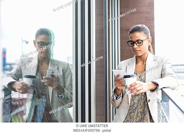Young woman on balcony with coffee to go and cell phone