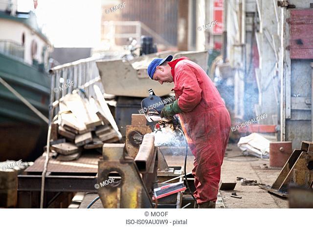 Worker welding girder in shipyard workshop