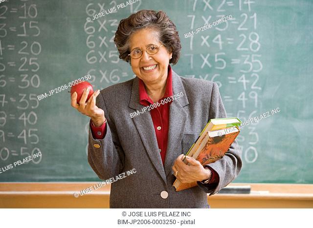 Senior Hispanic female teacher holding apple