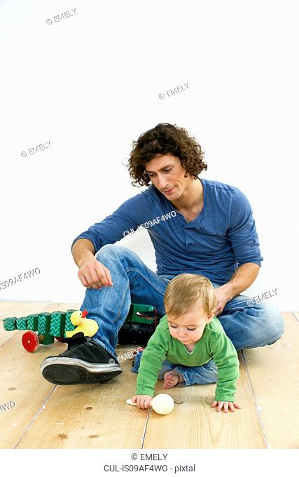 Studio shot of father and baby daughter paying on floor