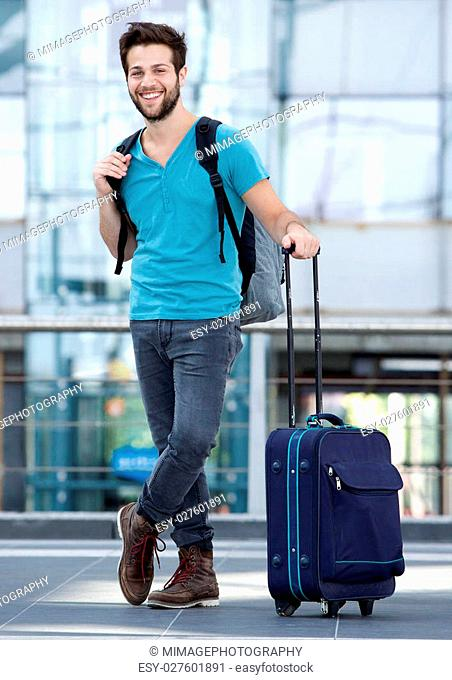 Full length portrait of a happy young man waiting at airport with suitcase and bag