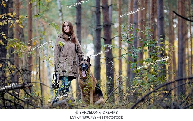 Young attractive girl and her pet - german shepherd - walking on a autumn forest, telephoto