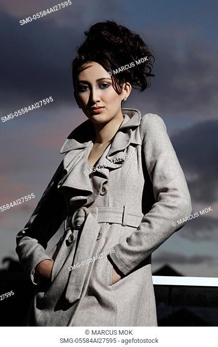 Asian woman wearing coat outside, dark clouds in background