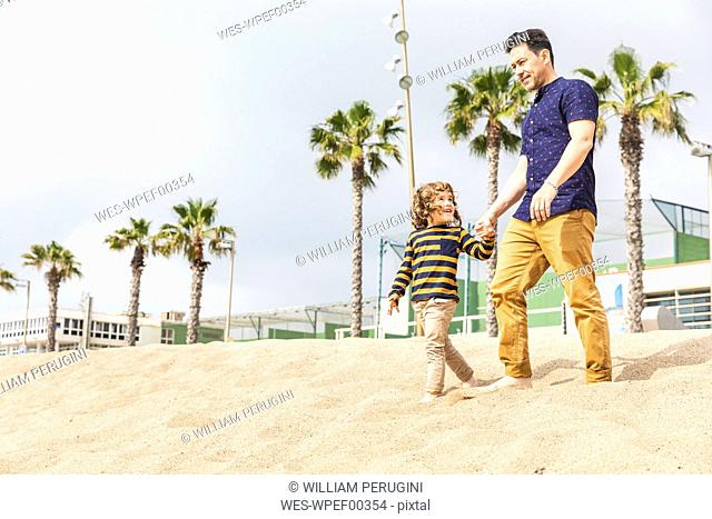 Spain, Barcelona, father and son walking hand in hand on the beach