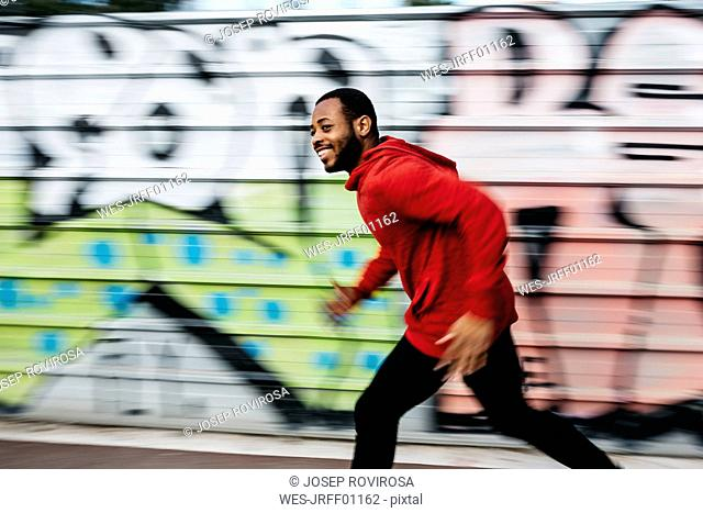 Smiling young man wearing red hoodie running along a graffiti wall