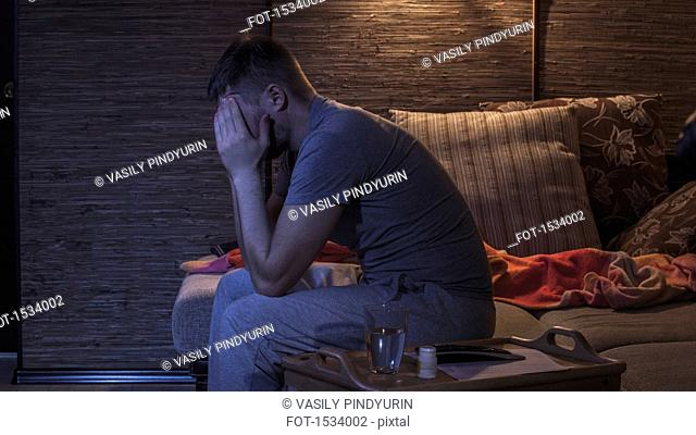 Side view of man suffering from headache while sitting on sofa