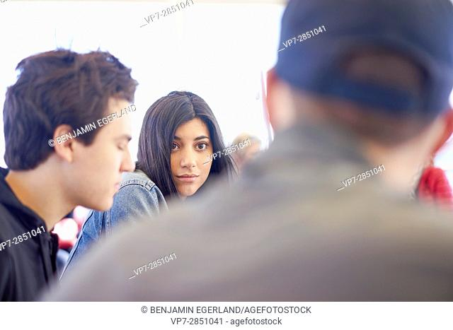 Attentive young girl listening to conversation with friends