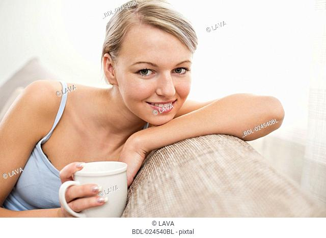 portrait of young woman with coffee cup relaxing on sofa