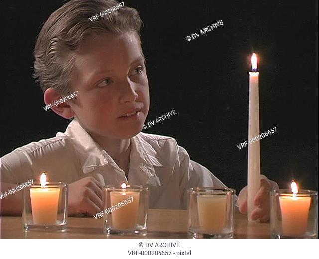 A boy lights candles