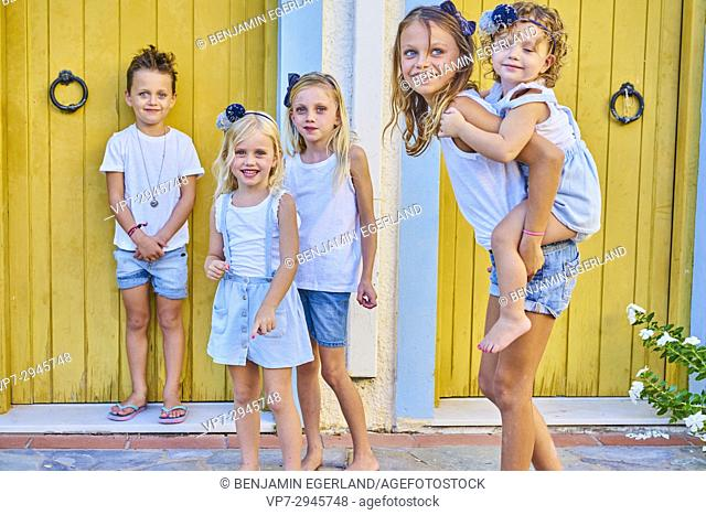 five siblings together in front of door. Australian ethnicity. During holiday stay in Hersonissos, Crete, Greece