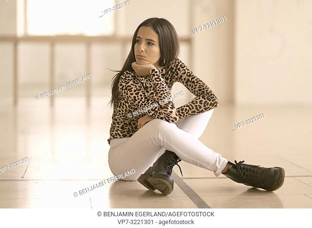 defiant woman sitting on floor, curling lips, pout, wearing fashionable leopard print sweater, looking thoughtful to side, in Munich, Germany