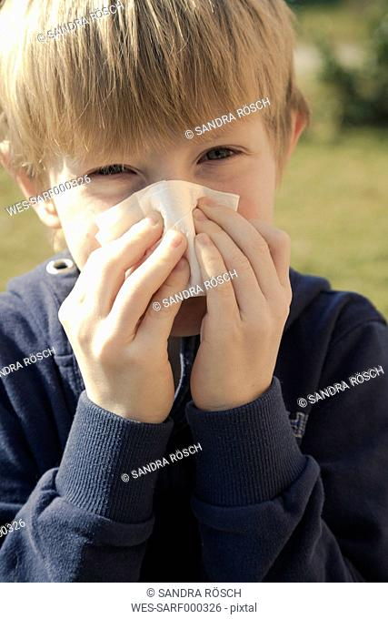 Portrait of boy blowing his nose with tissue handkerchief
