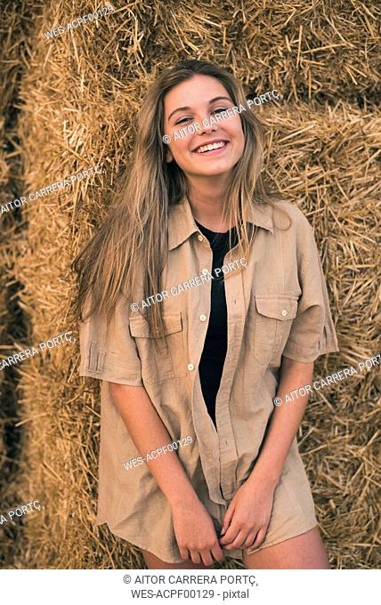 Beautiful young woman standing in front of hay bales, portrait