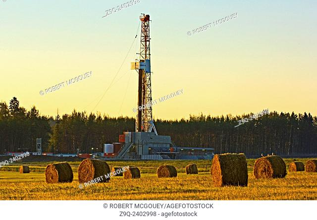 A land based drilling rig exploring for underground gas and oil in a farm field bathed in the warm morning sun light in rural Alberta, Canada