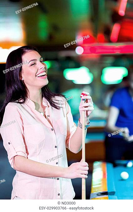 Young beautiful woman chalking the snooker cue and smiling in a club