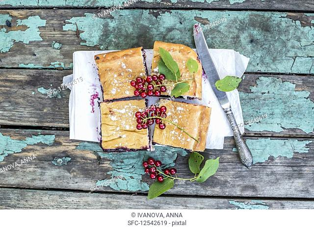 Blueberry pie pieces over a rustic painted wooden desk