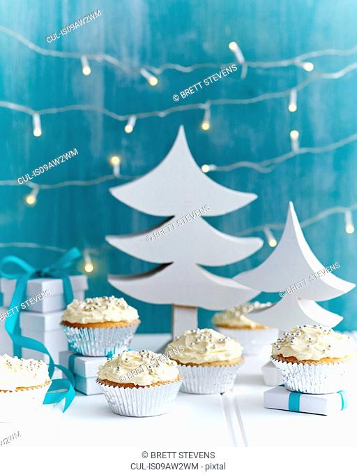 Christmas cupcakes decorated with silver cake decorations in festive setting