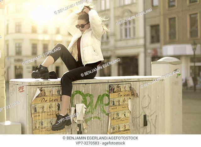 young cool woman sitting on electricity box, in city Cottbus, Brandenburg, Germany