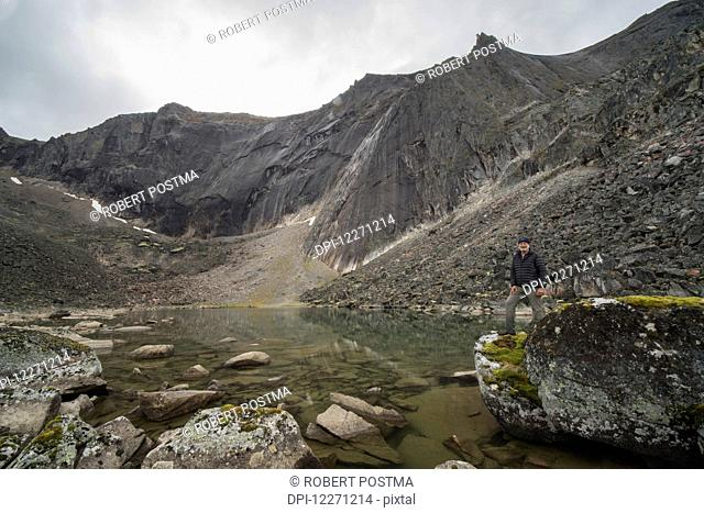 Man standing on a rock beside an unnamed lake in the Tombstone Mountains; Yukon Territory, Canada