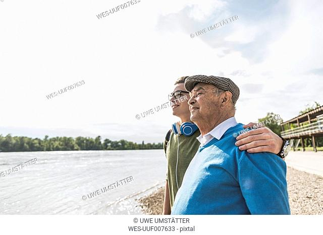 Grandfather and grandson at riverside looking together at distance