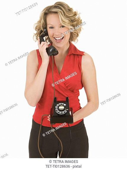 Woman talking on rotary telephone