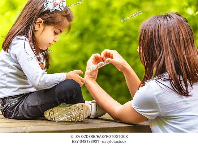 Young mom shows her little girl how to make heart shape on bench in forest. Happy mother and daughter moments with love and natural emotion