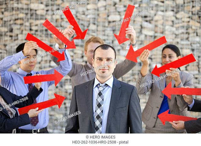 Group of business people pointing arrows towards businessman