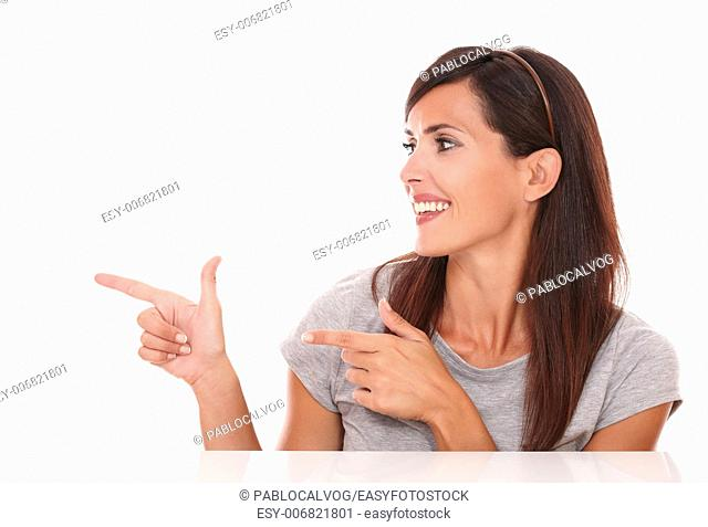 Portrait of beautiful brunette pointing her finger and looking to her right while smiling on isolated white background - copyspace