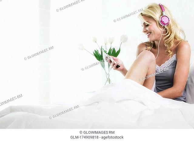 Young woman listening to an MP3 player and smiling
