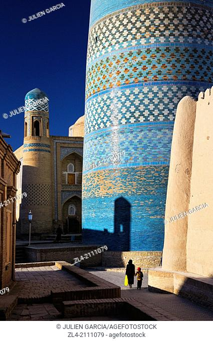 Woman and her son walking by the unfinished minaret Kalta Minor. Uzbekistan, Khorezm, Khiva, Itchan Kala (inner town)