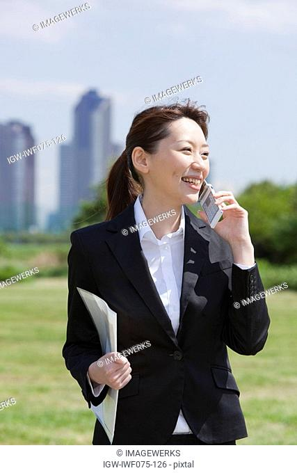 Japan, Tokyo Prefecture, Businesswoman using mobile phone, smiling