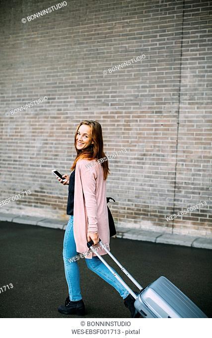 Walking woman with wheeled luggage