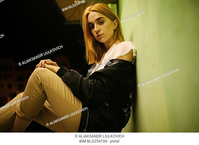Pensive Caucasian woman leaning against wall