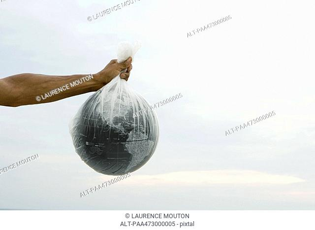 Cropped view of arm holding globe in plastic bag