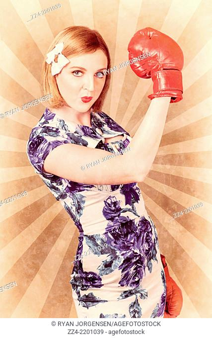 Old fashion photograph of a retro pinup boxing girl fist pumping glove hand into the air when celebrating a vintage victory