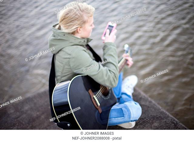Girl with guitar and mobile phone on pier