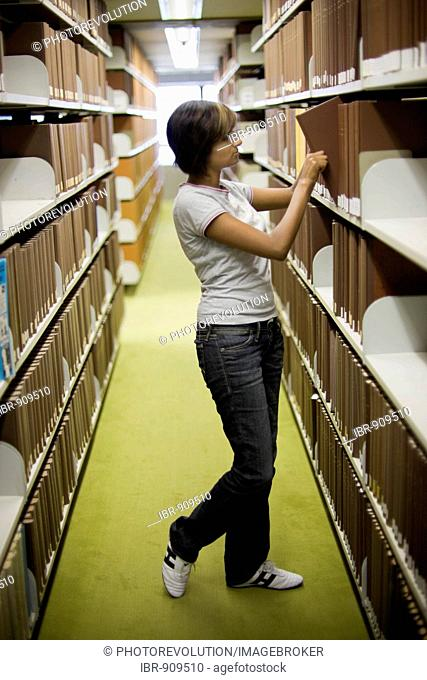 Young dark-haired female student reaching for a book from a bookshelf in a library