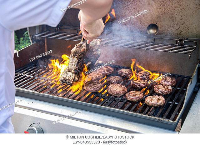 Marinated lamb joint and beef burgers cooking on a barbecue