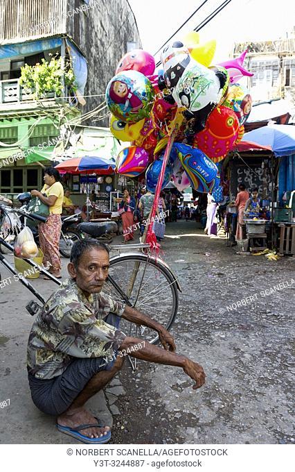 Myanmar (formerly Burma). Mon State. Mawlamyine (Moulmein). Balloon salesman in the street
