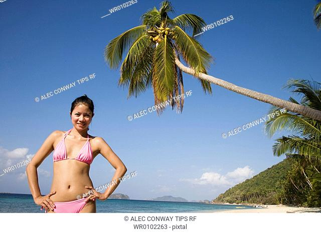 Philippines, El Nido bay. Philippino woman standing on the beach