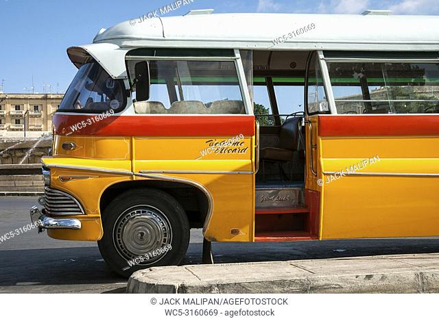 vintage orange british bedford buses on street of la valletta old town malta